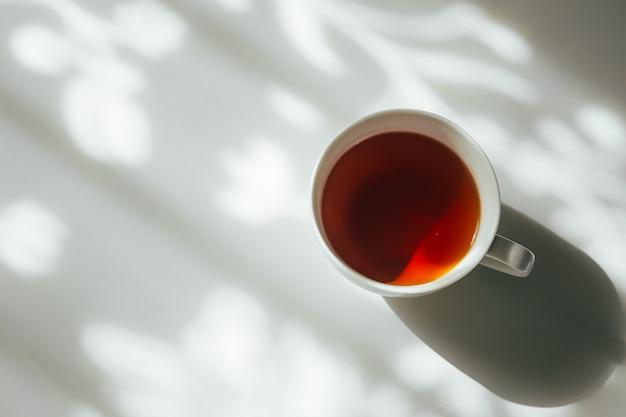 Tasse blanche de thé sur l'ombre du rideau naturel qui tombe sur la table blanche