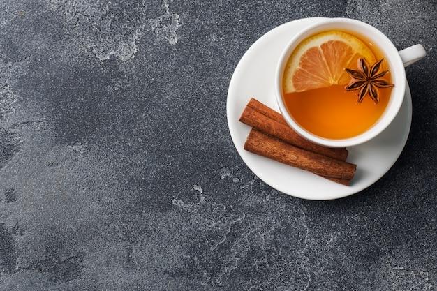 Tasse blanche avec tisane naturelle au citron et à la cannelle.
