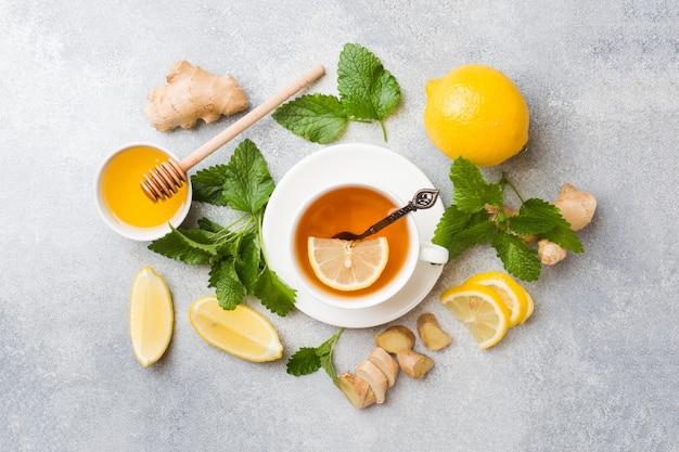 Tasse blanche avec tisane naturelle au gingembre, citron, menthe et miel.