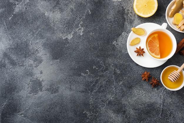 Tasse blanche avec tisane naturelle au gingembre, citron et miel à la cannelle.