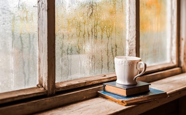 Tasse blanche et vieux livres