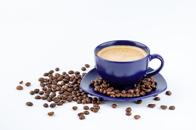 Tasse bleue de café et de grains de café sur un plateau sur fond blanc