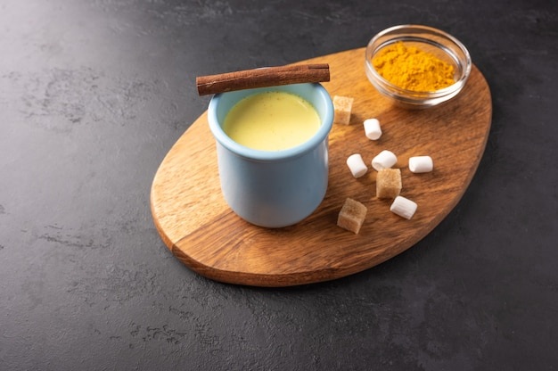 Tasse bleue en céramique avec du thé chai masala indien traditionnel avec de la cannelle et du sucre sur une planche à découper