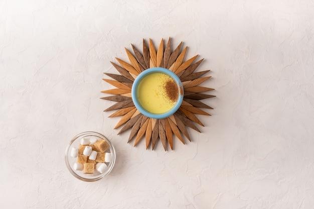 Tasse bleue en céramique avec thé chai masala indien traditionnel sur un support en bambou sous la forme du soleil