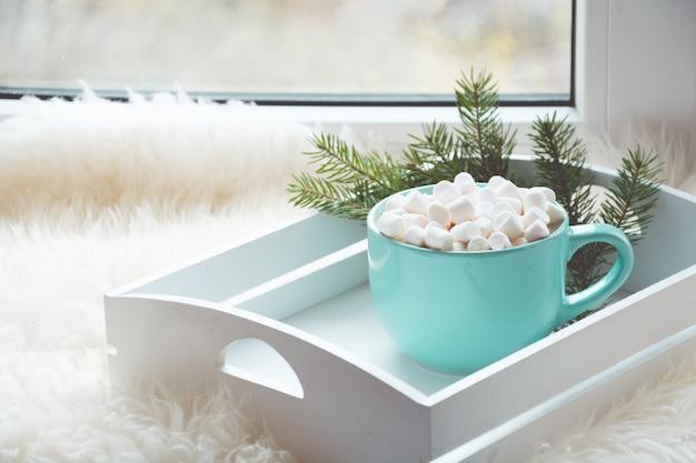 Tasse bleue de chocolat chaud à la guimauve sur le rebord de la fenêtre avec pelleterie pour se détendre