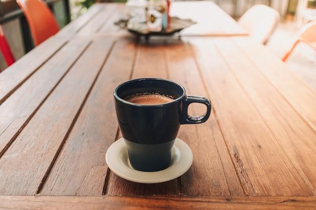Tasse bleue de chocolat chaud sur une table en bois dans un café