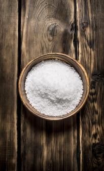 Tasse en bois avec du sel sur un fond en bois