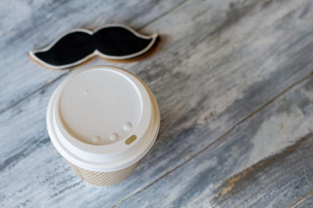 Tasse de boisson chaude et biscuit. biscuit moustache de couleur noire. dessert pour les vrais hommes. thé et pâtisserie au café.