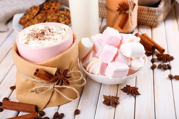 Tasse de boisson chaude décorée en feutre sur table en bois