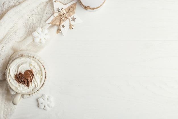 Une tasse de boisson chaude d'hiver avec de la crème fouettée et un foulard sur une table en bois