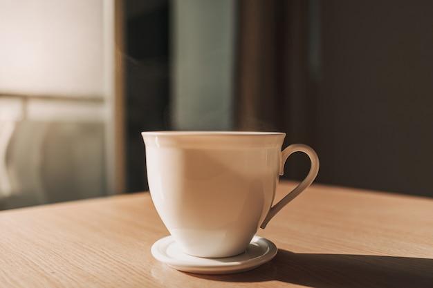 Tasse de boisson chaude sur la table à la lumière du soleil du matin calme