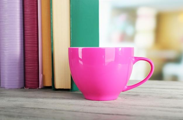 Tasse de boisson de couleur avec des livres sur la table en bois