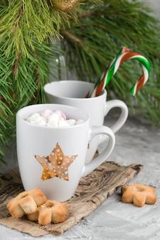 Tasse avec boisson décorée de biscuits à la guimauve et en forme d'étoile près de branches de sapin à feuilles persistantes branches de béton gris