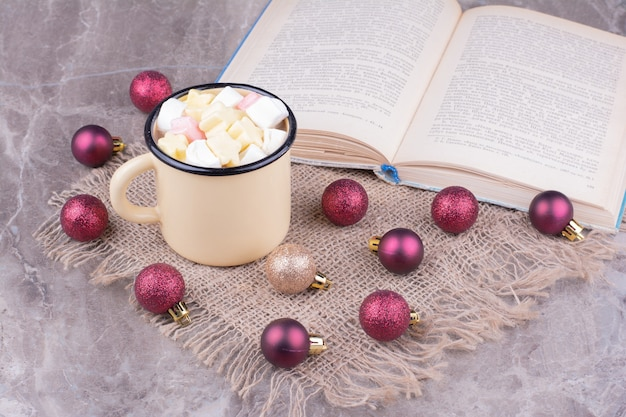 Une tasse de boisson à la guimauve avec des boules de sapin de noël rouges autour