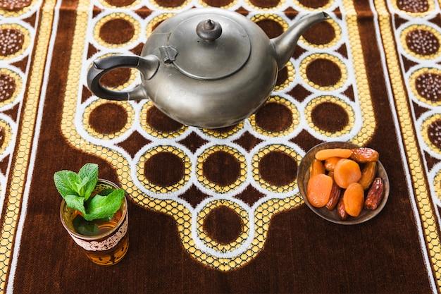 Tasse de boisson près de théière rétro et fruits secs sur tapis