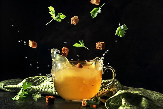 Une tasse de bouillon avec des ingrédients volants et éclabousse sur une obscurité.