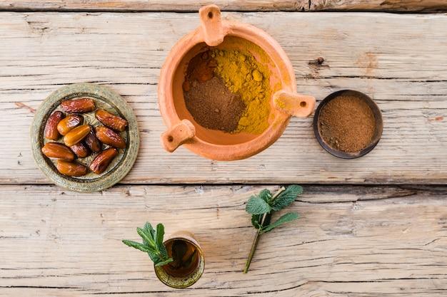 Tasse avec brindille près de fruits secs et d'épices dans un bol