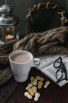 Tasse de cacao blanc sur une vieille table en bois avec un livre amusant et des lunettes de lecture.