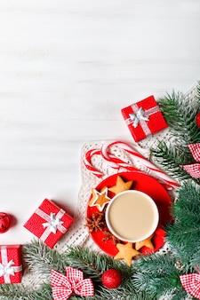 Tasse de cacao, cadeaux et branches de sapin sur une table en bois blanche