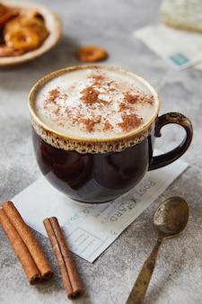 Tasse de cacao ou de café avec de la cannelle au lait et des biscuits sur fond gris clair.