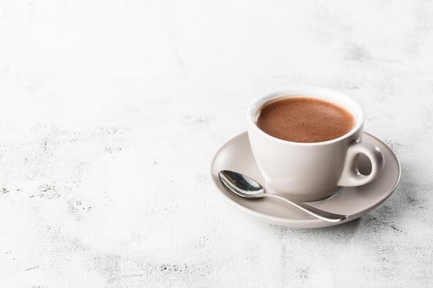 Tasse de cacao chaud ou chocolat chaud ou americano dans une tasse blanche isolée sur fond de marbre brillant. vue aérienne, espace copie. publicité pour le menu du café. menu du café. photo verticale. traditionnel
