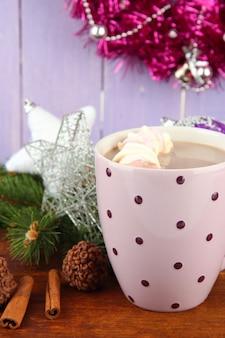 Tasse de cacao chaud avec des chocolats et des décorations de noël sur table sur fond de bois