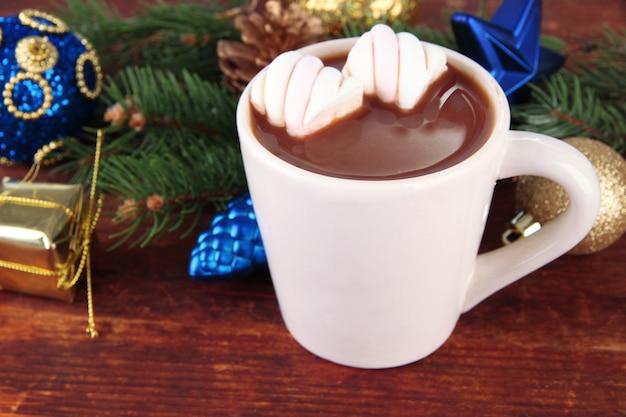 Tasse de cacao chaud avec des décorations de noël sur fond de bois