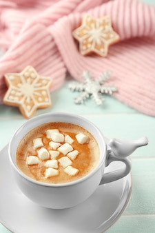 Tasse de cacao chaud avec guimauve, biscuits et écharpe chaude sur table bleue