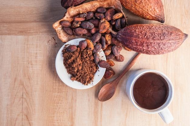 Tasse de cacao chaud avec de la poudre de cacao et des fèves de cacao sur fond de bois
