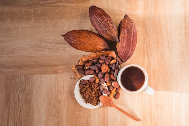 Tasse de cacao chaud avec de la poudre de cacao et des fèves de cacao sur une table en bois