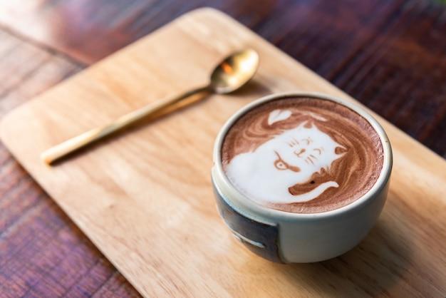Tasse de cacao chaud surmontant la forme d'un chat avec une cuillère sur une plaque de bois