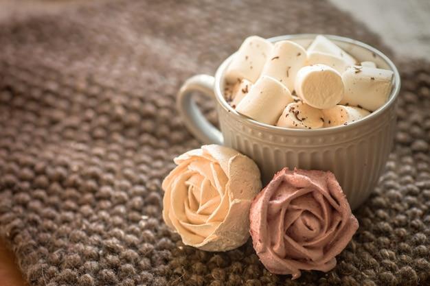 Tasse de cacao ou de chocolat chaud à côté de guimauve en forme de rose.