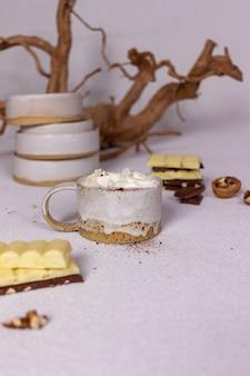 Une tasse de cacao à la crème et au chocolat sur fond clair