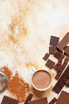 Tasse de cacao sur fond de marbre clair. assortiment de différents types de chocolat et de cacao en poudre. vue de dessus, pose à plat. espace pour le texte. verticale