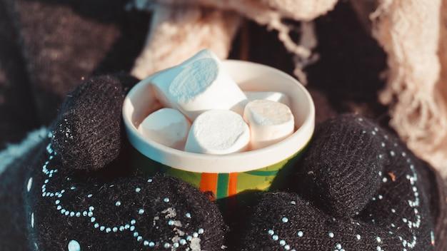 Une tasse de cacao avec des guimauves dans les mains en mitaines. fond d'hiver chaud. boisson réchauffante.