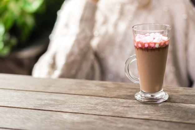 Une tasse de cacao et de guimauves se dresse sur une table en bois dans le contexte d'une fille assise. photo