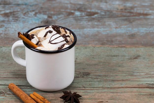 Tasse de cacao maison avec guimauves cannelle et anis étoilé sur bois
