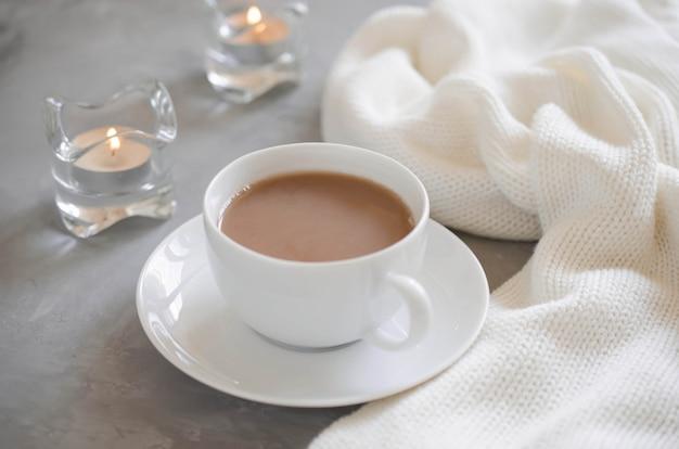 Tasse de cacao sur une table, bougies et couverture tricotée.