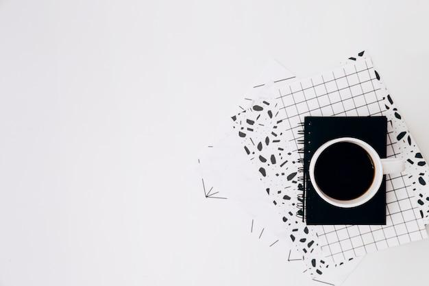 Tasse à café et agenda sur papiers à motif sur fond blanc