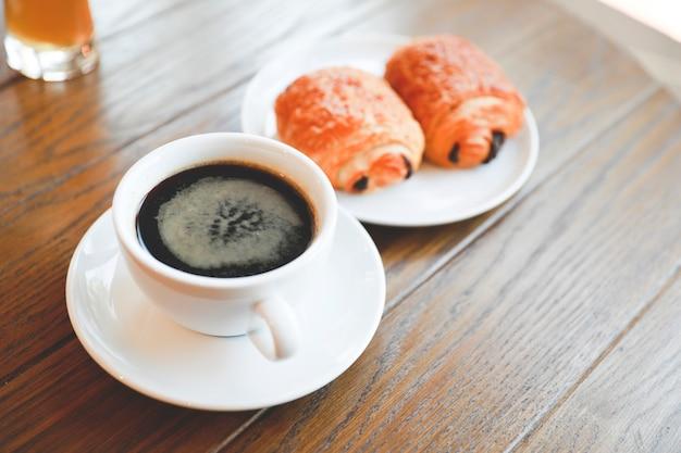 Tasse à café americano avec boulangerie servi sur une table en bois.