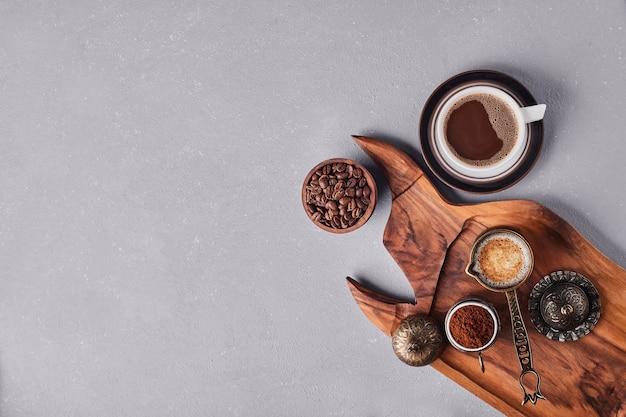 Une tasse de café avec de l'arabica et de la poudre autour.