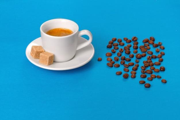 Tasse de café aromatique chaud avec des morceaux de sucre sur bleu