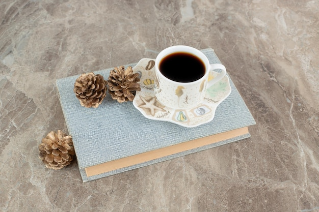 Tasse de café aromatique sur le dessus du livre avec des pommes de pin
