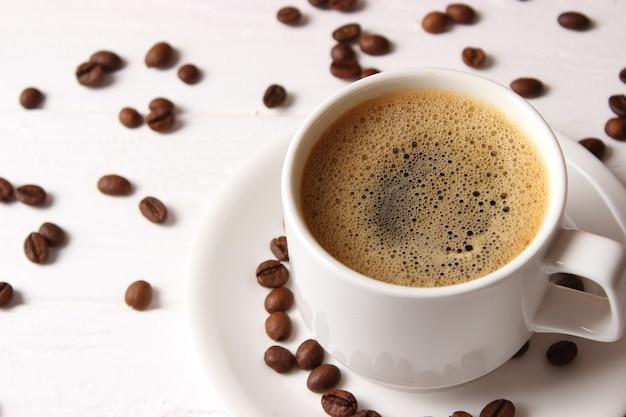 Tasse de café aromatique et grains de café sur un fond en bois. photo de haute qualité