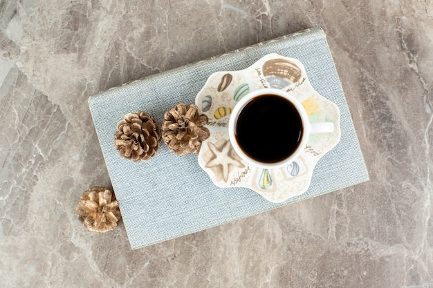 Tasse de café aromatique sur le livre avec des pommes de pin