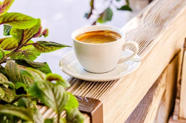 Tasse de café aromatique noir dans une tasse blanche sur une surface en bois