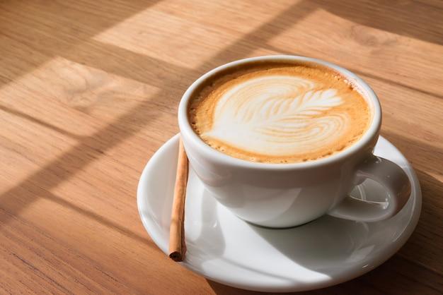 Une tasse de café d'art latte chaud sur une table en bois avec un livre dans le café-restaurant.