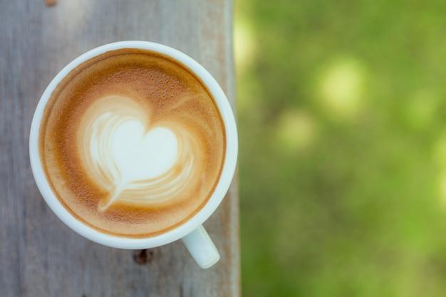 Une tasse de café d'art latte chaud sur une table en bois