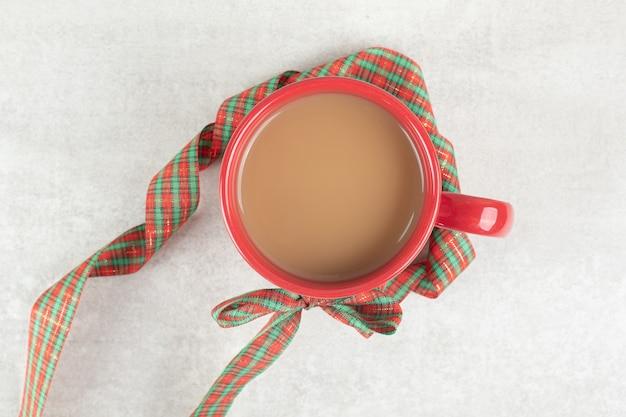 Tasse de café attachée avec un ruban sur une surface blanche