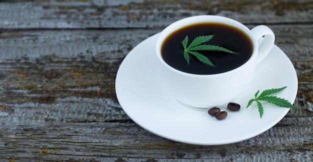 Tasse de café au cannabis avec des feuilles de chanvre et des grains de café torréfiés sur table en bois